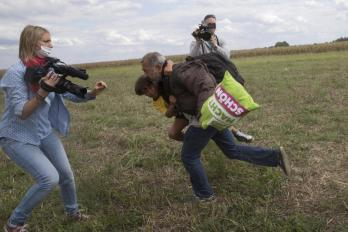 A migrant runs with a child before being tripped by a TV camerawoman (L) and falling as he tries to escape from a collection point in Roszke village, Hungary, September 8, 2015. REUTERS/Marko Djurica